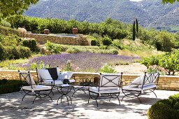 A terrace with metal chairs and cushions and a view of the Mediterranean landscape