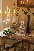 Burning candles in a glass candlestick and vases on a rustic wooden table