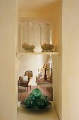 Glass jars on a shelf in a narrow niche with a view of an antique armchair