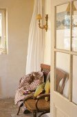 An open glass door - coffee break on an antique wooden bench with cushions and a blanket