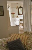 A cushion on a bed and view of an open bathroom with a bathtub and a light curtain