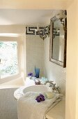 A bathroom in a country house - a curved basin with an antique mirror on a white mosaic-tiled wall