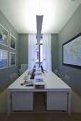 A white desk with indirect lighting in front of a grey wall