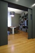 A designer apartment - a grey wall with a sliding door, a continuous parquet floor and a view into a living room