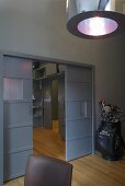 A grey room - a pendent lamp with a metal shade and sliding doors on a continuous parquet floor