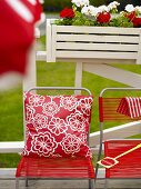 Garden chairs with red fabric covering and pillows in front of a railing with window boxes