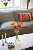 Flowers in a vase and candlesticks on a coffee table in from of a gray sofa with striped pillows