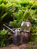 Watering can and torch next to a mini-greenhouse in the garden