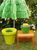 Yellow plastic plant pot and orange stool in front of green sun umbrella made from bast