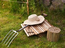 Wicker ladies hat on wooden tiles and pitchfork in the garden