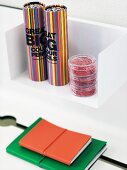 Boxes of bright colored pencils in cylindrical boxes on a white wall bracket and notebooks with coloured covers