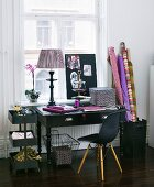 Work area in a mix of styles - black desk with Bauhaus chair in front of a window and bolts of fabric in a container
