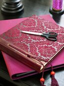 Photo album with red flora pattern and scissors