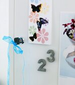 Door lock and key with blue ribbon and decorative butterflies on a cabinet