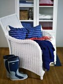 White wicker chair with blue pillows and galoshes in front of a display cabinet