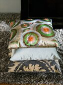 A stack of cushions with geometric and floral pattern on a flokati rug
