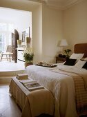 A traditional, open plan bedroom, double bed, ottoman, open doorway with steps to sitting room