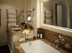 A detail of a traditional bathroom, showing a fitted bath with marble surround, wash basin set in unit, mirror