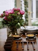 A detail of a modern dining table, Japanese bowls, chopsticks, arrangement of pink roses in glass vase