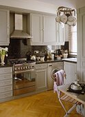 Kitchen with grey cupboards and stainless steel oven and extractor fan