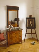 Artwork on easel next to chest of drawers with marble top