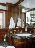 Mirror above washbasin set in wooden unit with marble top