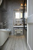 A rustic bathroom with grey walls and a washstand in the window niche