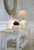 Vase and table lamp made from white ceramic with fabric shade on a table