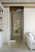 An open-plan living room with a white ladder against a cupboard and an antique Greek pillar in the hallway with an open door leading to a bedroom