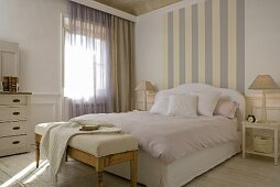 Striped wall paper at the head end of a double bed with pink bedclothes and an upholstered bench