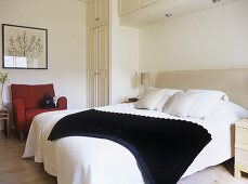 A modern bedroom in neutral colours, double bed, upholstered armchair, fitted wardrobes, upholstered headboard,