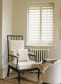 Corner of room in neutral colours with  shutters and a chair with a radiator