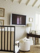 A detail of a traditional study room decorated in neutral colours, pattern wallpaper, beamed ceiling, wooden chair with cushions, ottoman, wall mounted television, table, lamp,