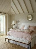 A detail of a traditional bedroom decorated in neutral colours, pattern wallpaper, beamed ceiling, double bed with upholstered headboard, bench seat, lamp, mirror, natural flooring,