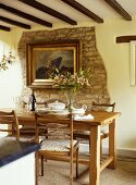 Dining room with a wooden table and chairs, artwork on an exposed stone wall.