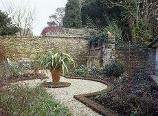 Walled garden with a pot plant central to a gravel path.