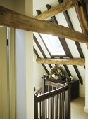 Beamed ceiling and wooden banister with a side table in an attic hallway.