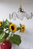 Pendant light in front of sunflowers in red vase