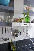 Utensils on hanging on bar above kitchen sink