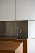 A sink with a tap against a stainless steel splash guard with white fitted cupboards above