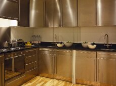 Contemporary kitchen with stainless steel units reflected in mirror