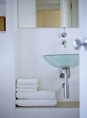 Bathroom with designer glass wash basin and folded towels on ledge.