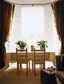 Dining room with table and chairs in window with drapes