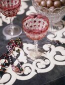 A detail of decorative wine glasses set on a painted table, glass vase,