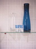 A detail of a modern bathroom, a glass shelf with blue glass vase, decorative glasses, mosaic tiles,