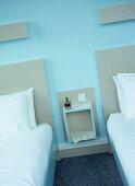 Twin beds in blue hotel bedroom