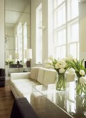 Vases of white tulips on clear plastic table