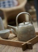 A detail of ceramic teapot and beakers on wooden tray,