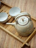 Ceramic teapot and beakers on wooden tray