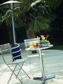 Garden furniture and outdoor heater on wooden decking.